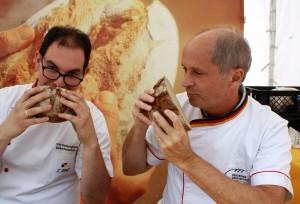 Zwei Brotprüfer riechen an je einem halben Laib Brot.