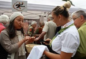 Eine Kundin mit einem Brotstück spricht mit einer Verkäuferin.